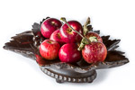 Black Forest Musical Fruit Bowl with Swiss musical movement, shown as centrepiece and deeply filled with deep red shiny apples