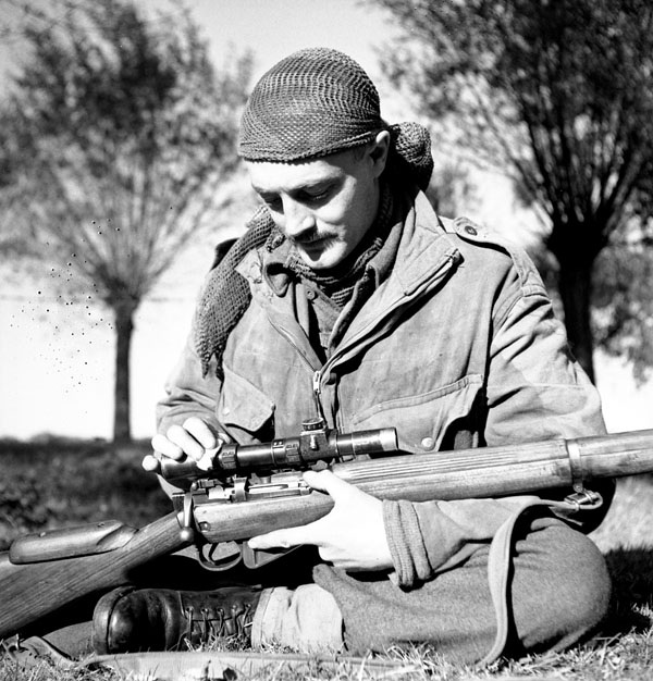 Sergeant H.A. Marshall of The Calgary Highlanders cleans the telescopic sight of his No.4, MkI(T) rifle during a scouting, stalking and sniping course, Kapellen, Belgium, 6 October 1944.