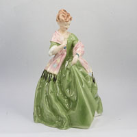 China figurine of lady in wide green dress with pink shawl trimmed in black